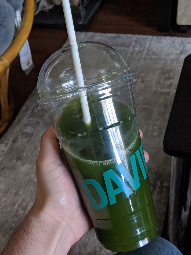 A large plastic cup of green matcha, the text DAVID in aqua coloring spans across it.