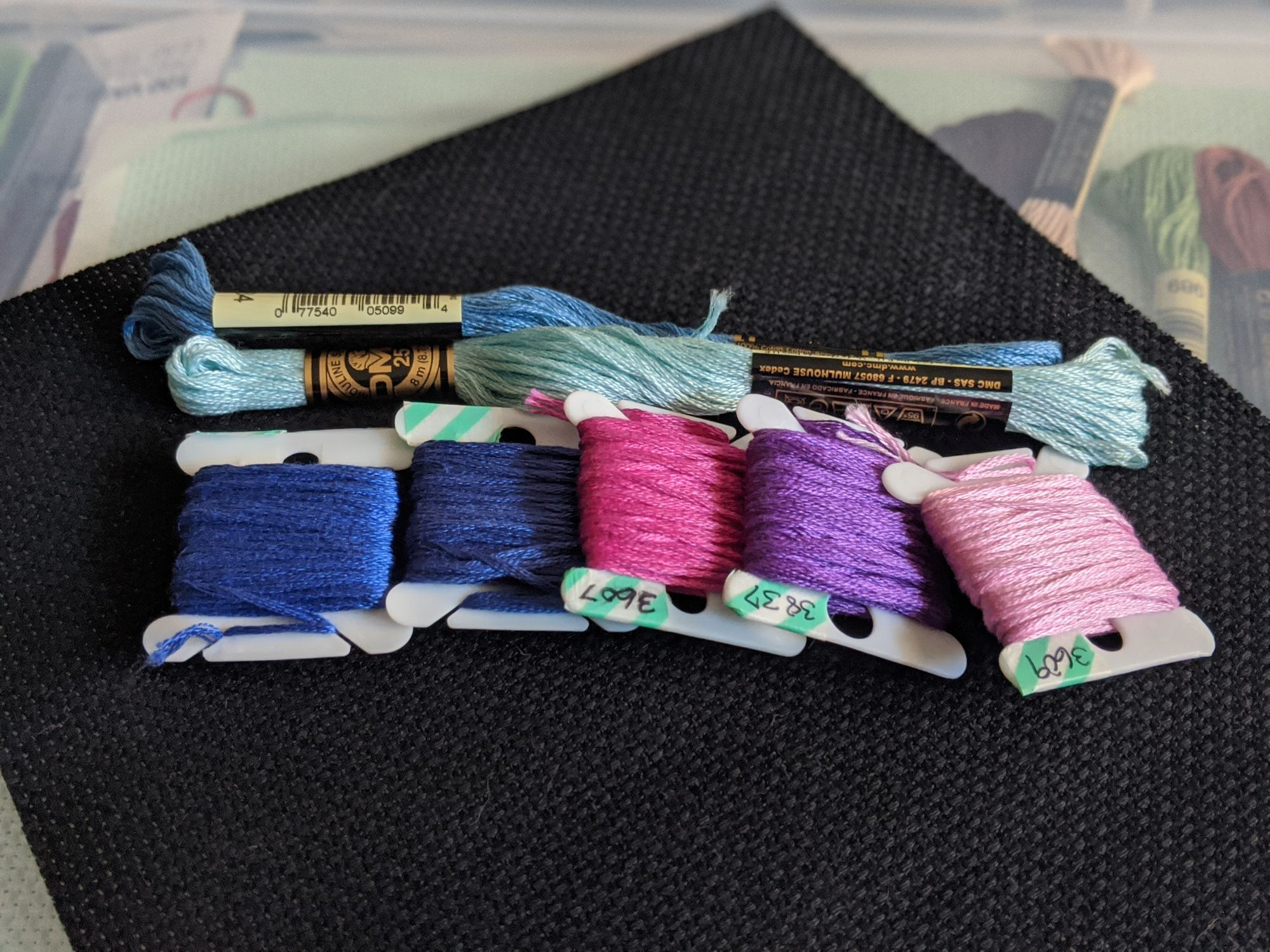 Different colored blue, pink, and purple thread sitting on top of black aida cloth, which is fabric you use for cross stitching
