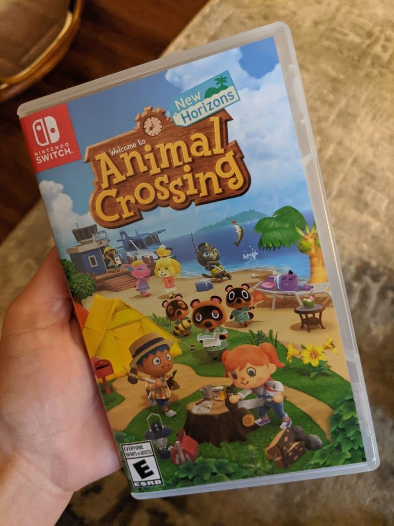Me holding up a physical copy of Animal Crossing: New Horizons for the Nintendo Switch