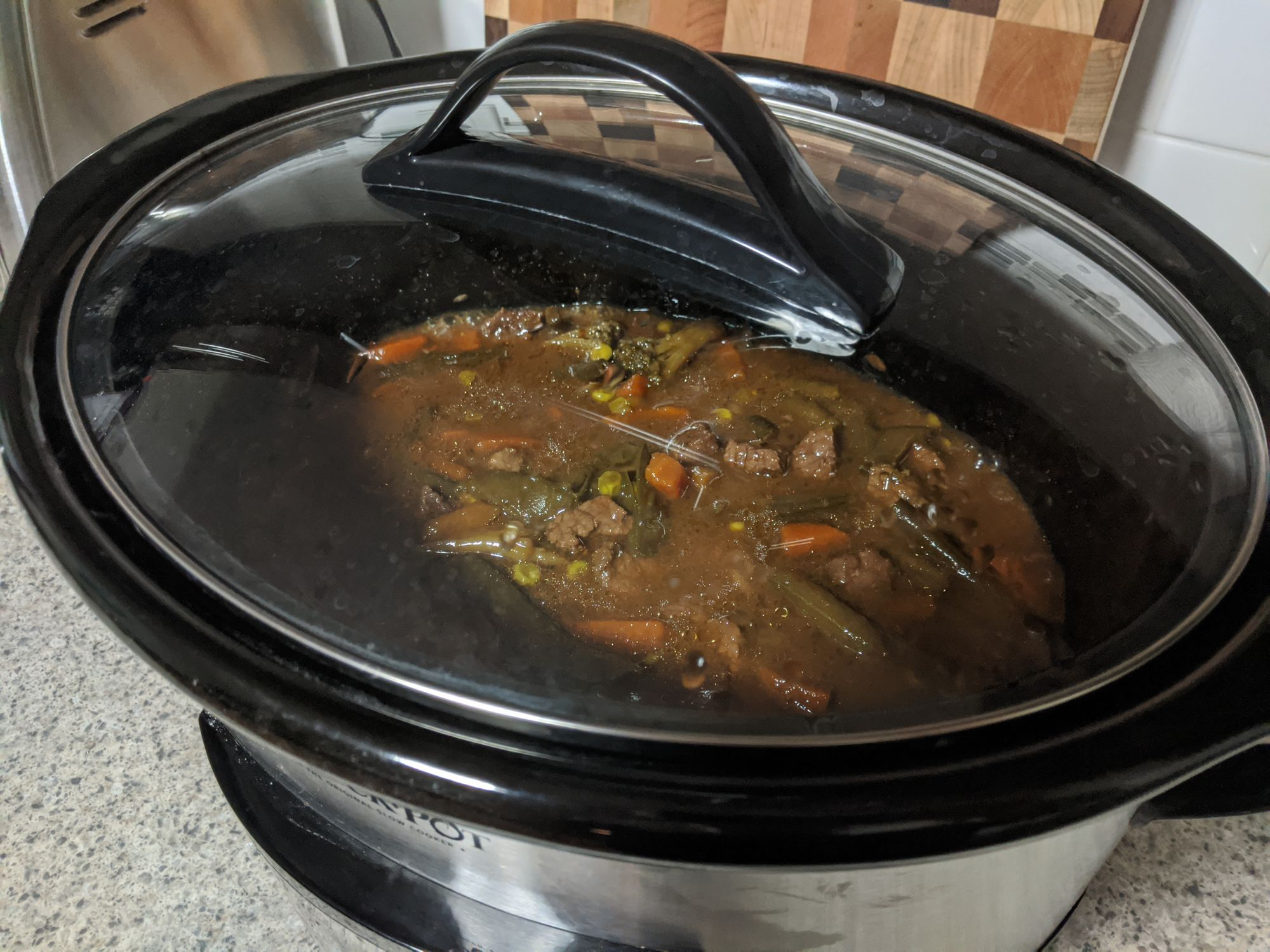 A picture taken of a slow cooker from the top view. You can see through the glass cover inside, where a beef stew looking meal is cooking away.