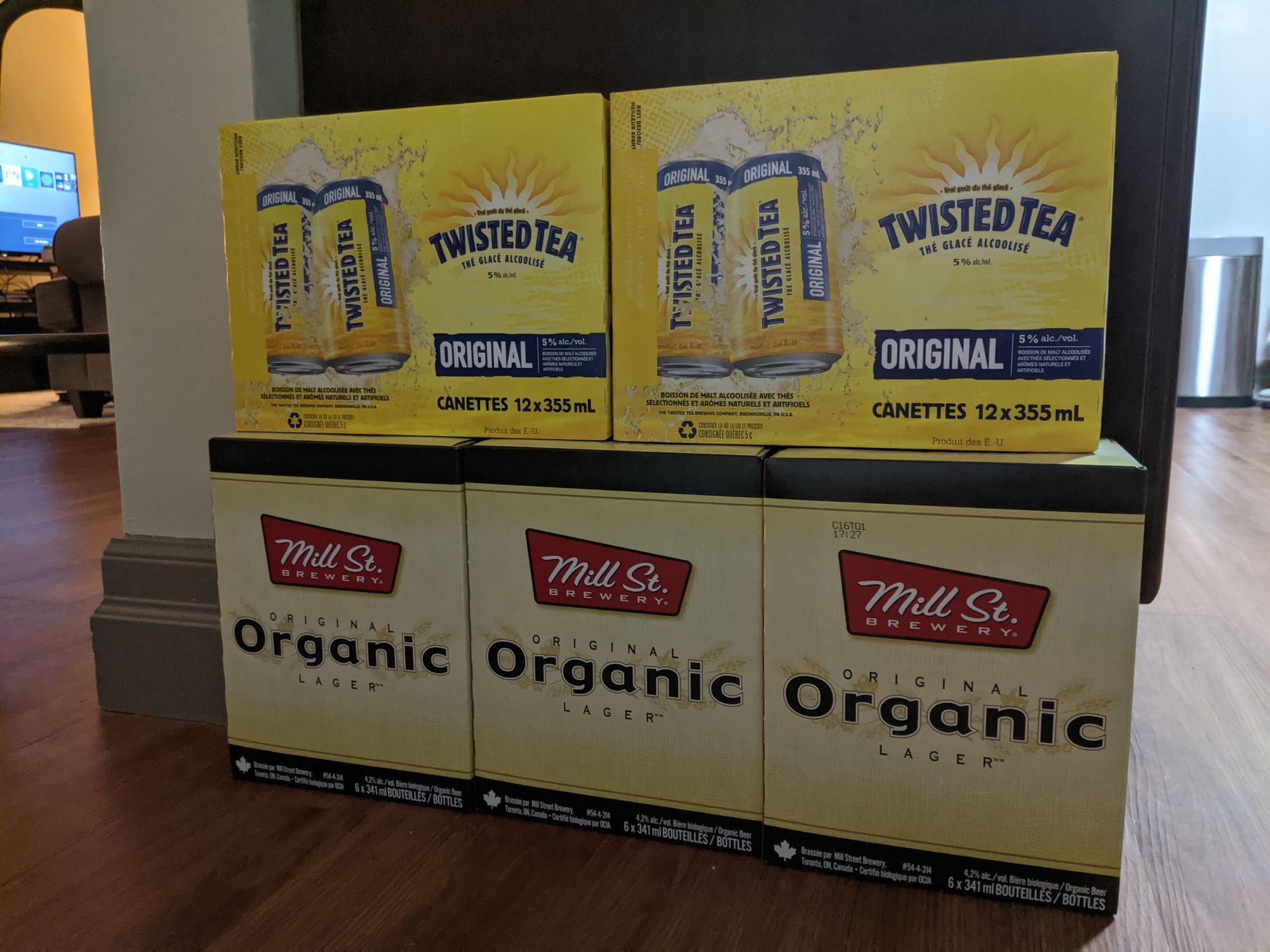 Boxes of alcohol on the floor. Twisted Teas stacked on top of multiple boxes of Mill St. Organic beer