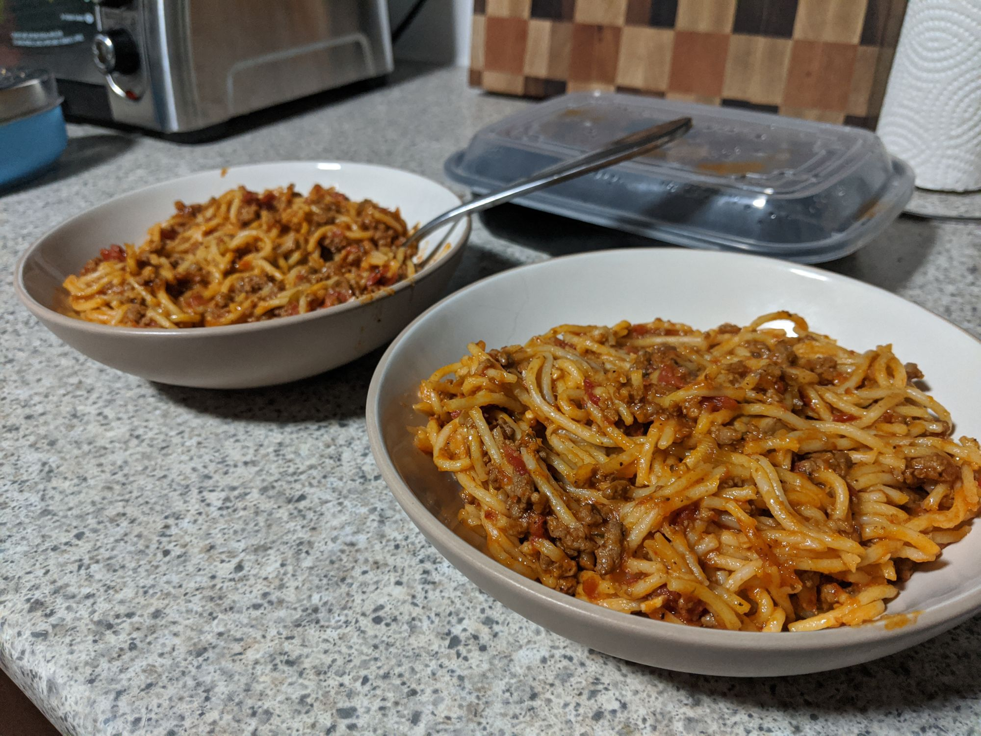 Two bowls sitting on a counter, both filled with spagetti and meat sauce!