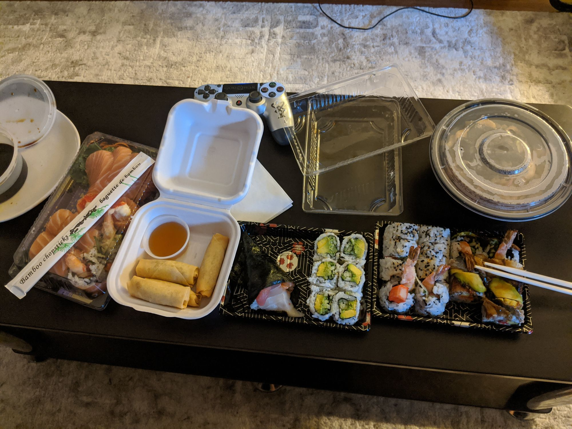 A top down image of take out sushi on our black coffee table.