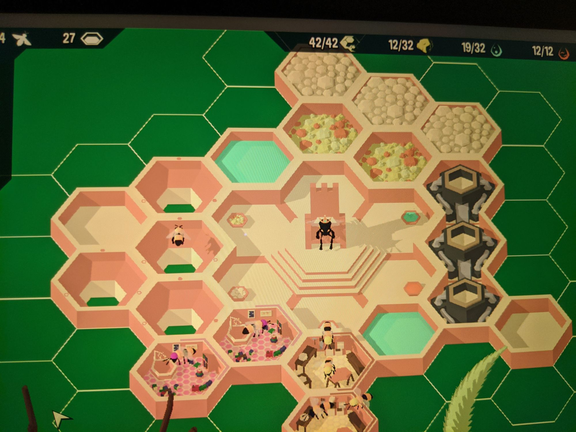 A phone picture of the game Hive Time, a queen bee sits on her thrown and there are hexagon rooms around her with various uses.
