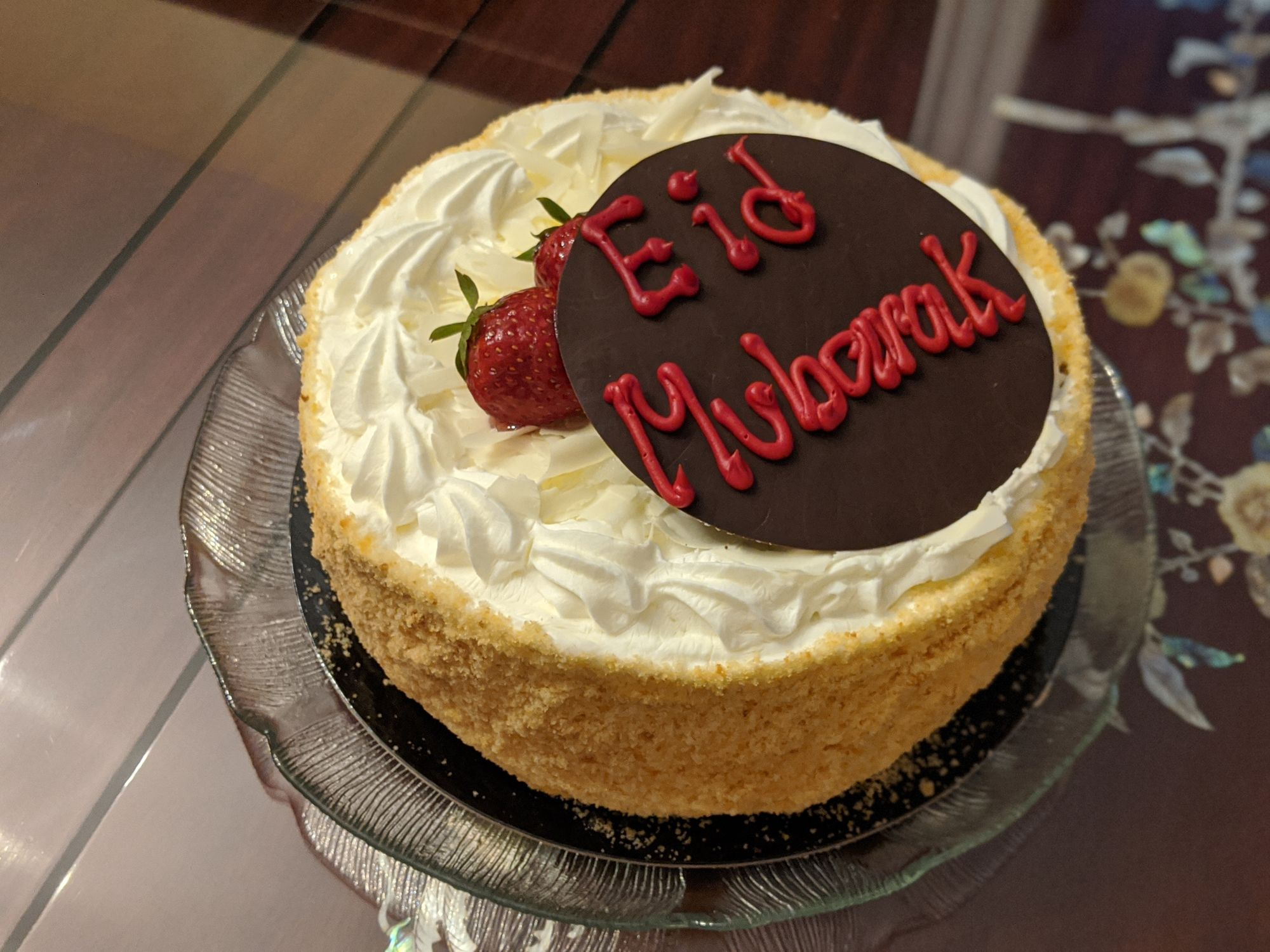 A strawberry shortcake with breadcrumbs around the sides, white icing on top and two strawberries holding up a small chocolate plate that says Eid Mubarak.up