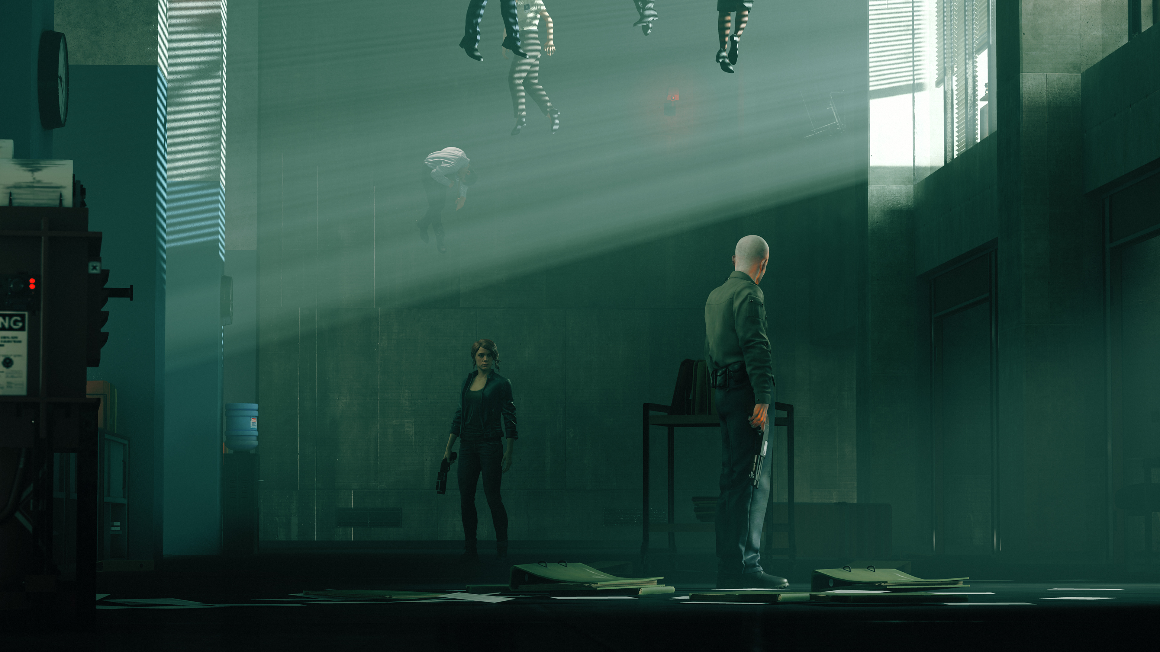 Jesse Faden from Control standing tensely infront of a bald man. The photo is very green hued and there are bodied floating near the roof.
