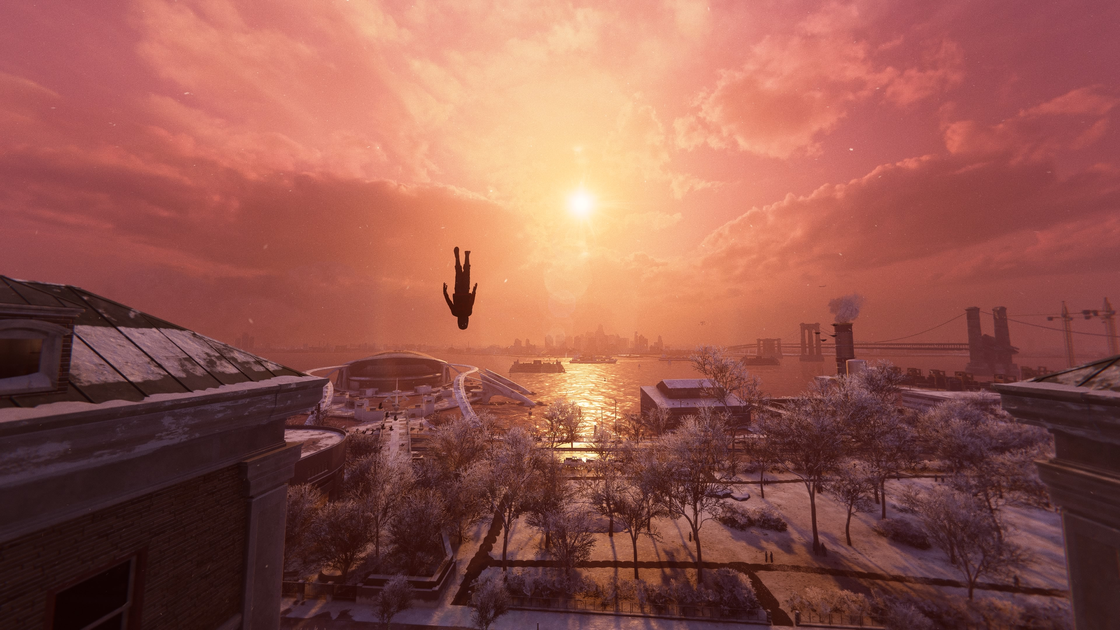 Miles falling in front of a sunset over the city. He is fully upside down.