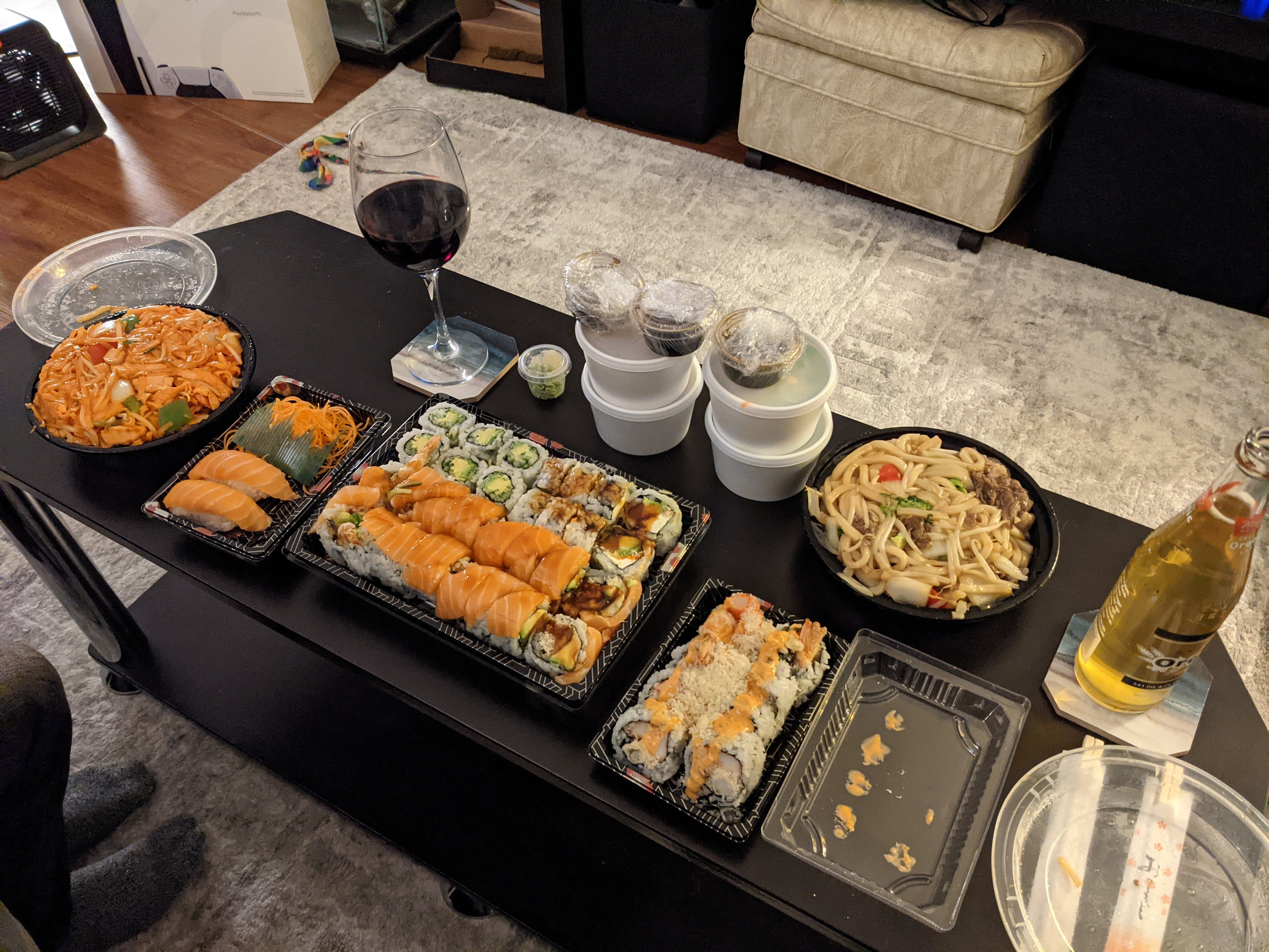 A variety of sushi dishes layed out on a black coffee table. It's lots of food with a beer and wine glass as well.