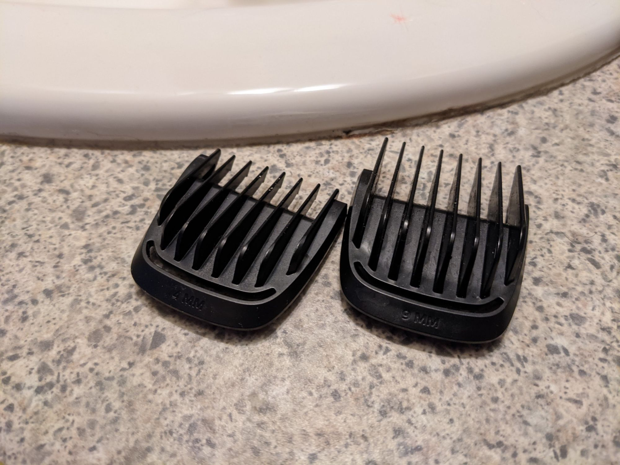 Two black clipper guards sitting on a bathroom counter.