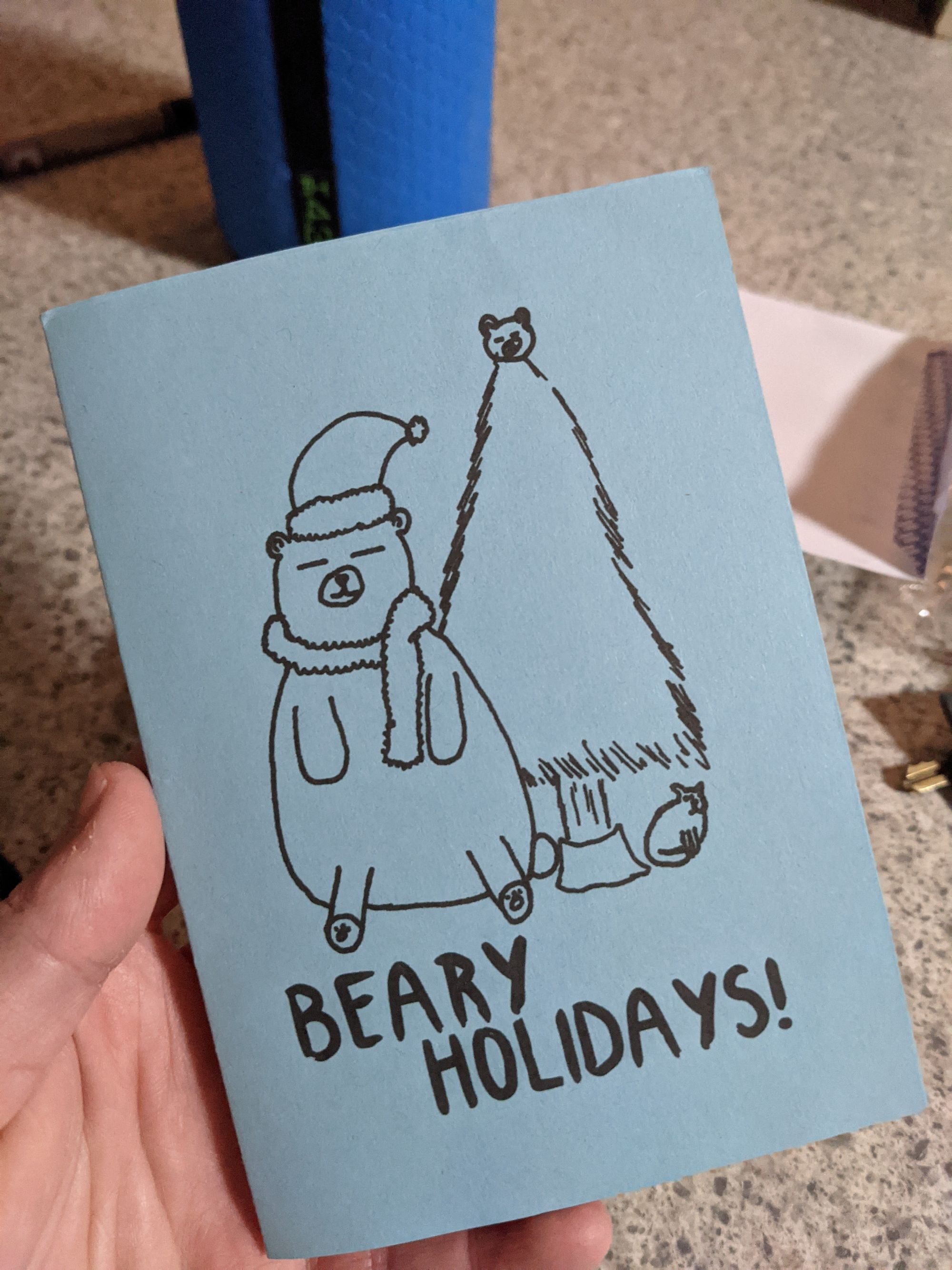 My hand holding a blue christmas card, is says Beary Holidays! with a drawn bear next to a christmas tree.