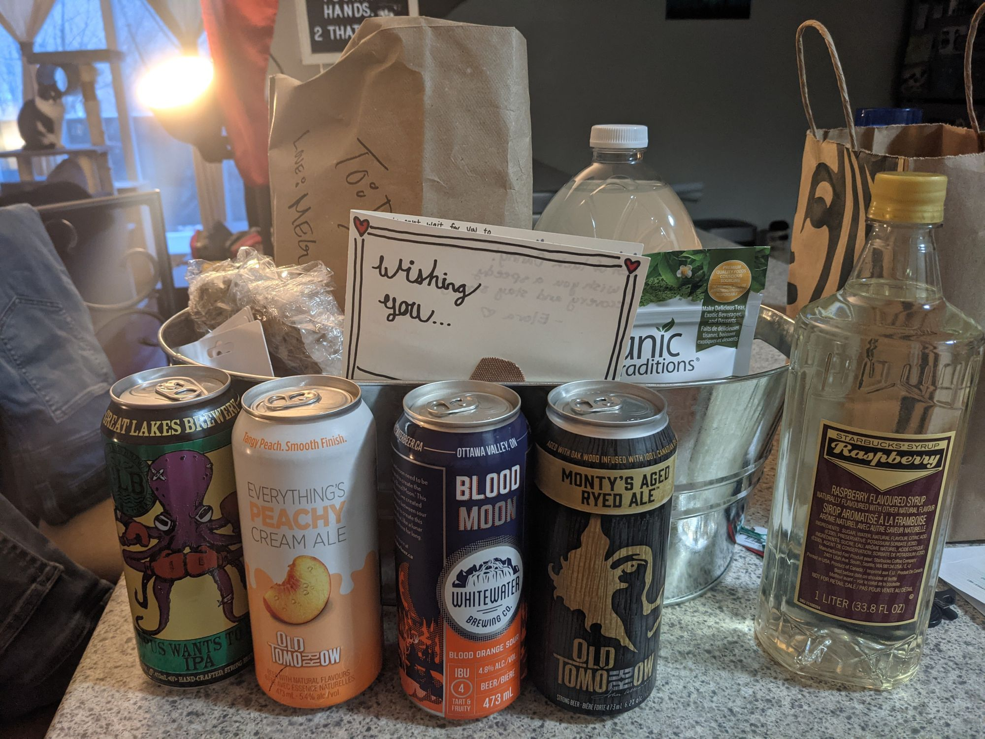 A gift basket with various items: four individual cans of beer & cider, raspberry sugar syrup, lemonade, matcha powder, various baked goods.